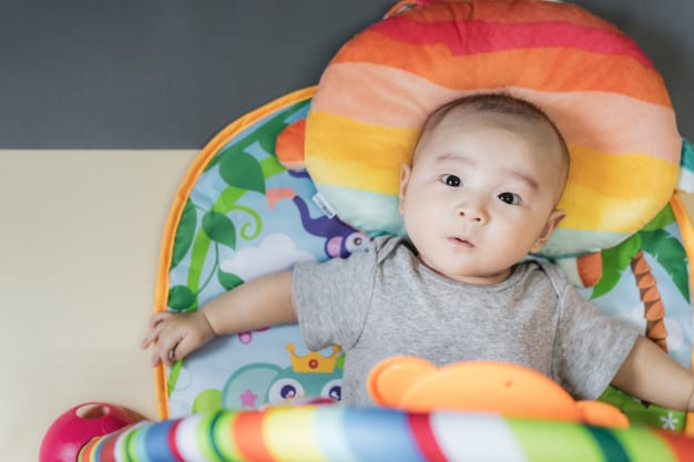 Asian baby lay down on colorful play gym. new family, protection ...